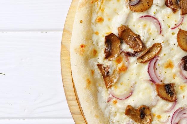 Pizza con champiñones y cebolla a bordo en la mesa de madera blanca de cerca