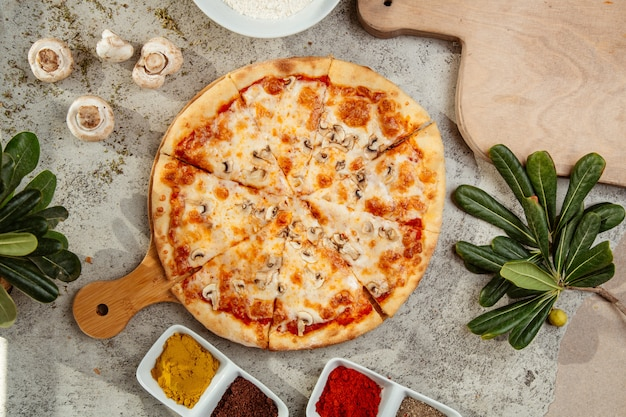 Pizza de champiñones con champiñones y especias sobre la mesa