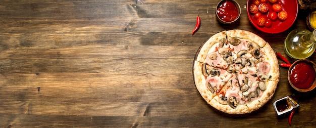 Pizza con champiñones y jamón. sobre una mesa de madera.