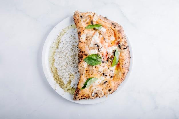 Pizza con champiñones, mozarella y hojas basílicas.