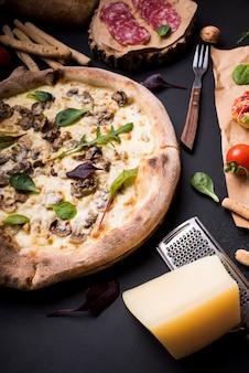 Pizza de champiñones con queso y rallador cerca de ingredientes sobre fondo negro