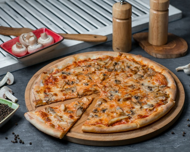 Pizza de champiñones, una rebanada cortada en una tabla de madera
