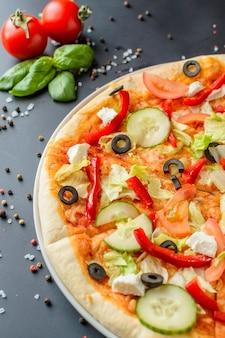 Pizza cocida en un oscuro con ingredientes, primer plano