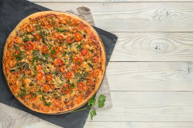 Pizza cocida en una vista superior de fondo de madera