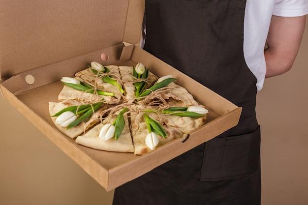 Pizza creativa con tulipanes de flores en caja de papel servida por el camarero