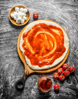 Pizza cruda. masa extendida con pasta de tomate, mozzarella y tomates frescos. sobre fondo rústico