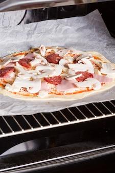 Pizza cruda sobre papel pergamino colocada en el horno.