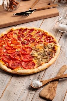 Pizza de cuatro estaciones surtidas en la mesa de madera