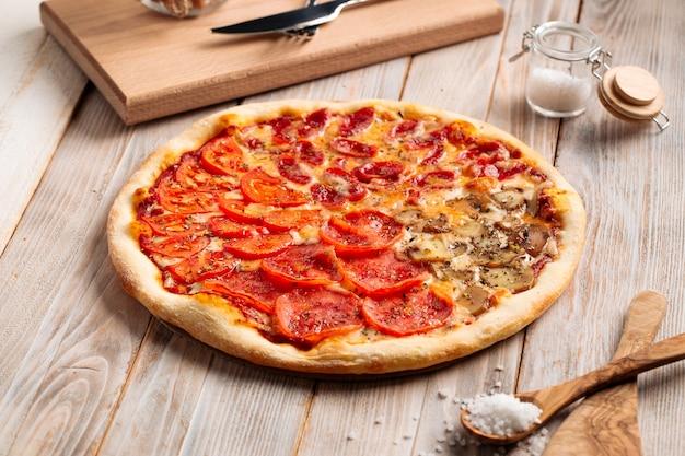 Pizza de cuatro estaciones surtidas en la mesa rústica de madera