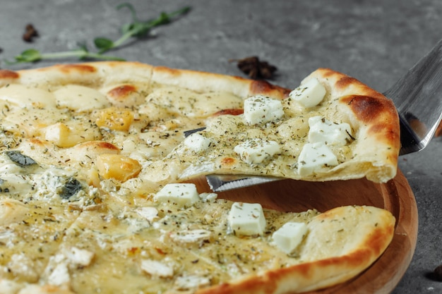 Pizza de cuatro quesos, pizza italiana. pizza rellena con cuatro variedades de queso sobre un fondo gris.