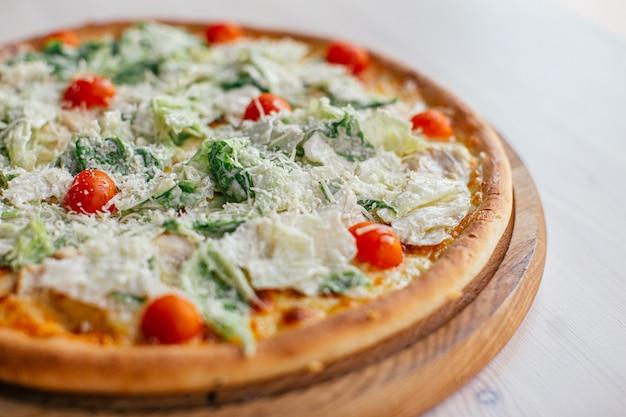 Pizza deliciosa fresca con lechuga y tomates cherry