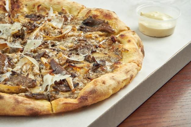 Pizza con diferentes champiñones, parmesano y salsa blanca en una caja de cartón con salsa para los lados en una mesa de madera