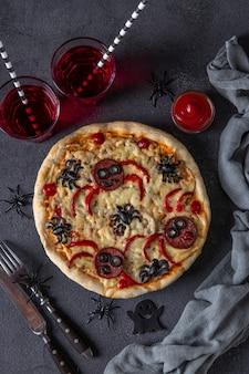 Pizza divertida de halloween con arañas, idea creativa para pizza de halloween sobre fondo gris oscuro con bebidas y decoraciones
