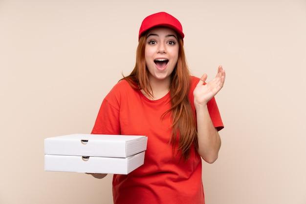 Pizza entrega adolescente mujer sosteniendo una pizza con expresión facial sorpresa