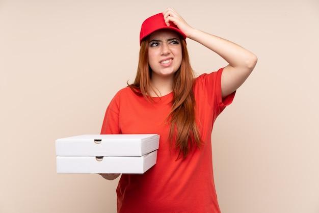 Pizza entrega mujer adolescente sosteniendo una pizza con dudas y con expresión de la cara confusa
