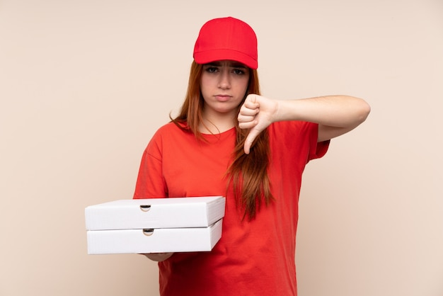 Pizza entrega mujer adolescente sosteniendo una pizza mostrando el pulgar hacia abajo signo