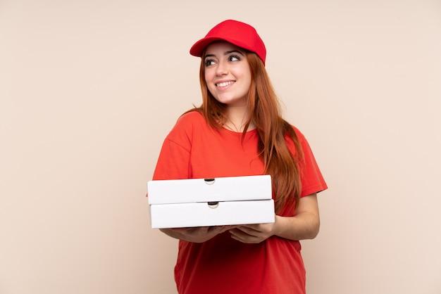 Pizza entrega mujer adolescente sosteniendo una pizza riendo y mirando hacia arriba