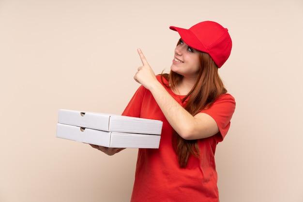Pizza entrega mujer adolescente sosteniendo una pizza señalando con el dedo índice una gran idea