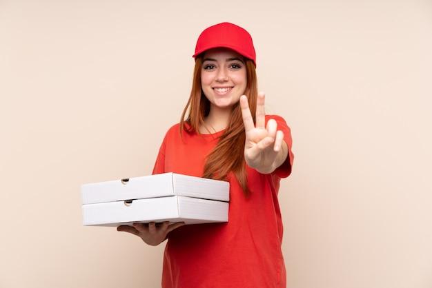 Pizza entrega mujer adolescente sosteniendo una pizza sonriendo y mostrando el signo de la victoria