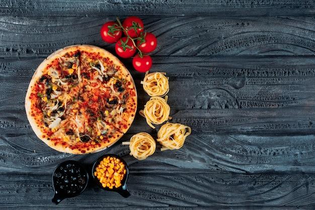 Pizza con espagueti, tomate, aceitunas, vista superior de maíz sobre un fondo azul oscuro