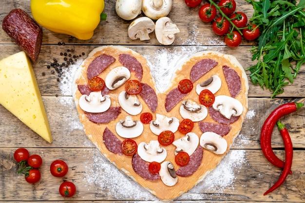 Pizza en forma de corazón e ingredientes para el día de san valentín, proceso de cocción