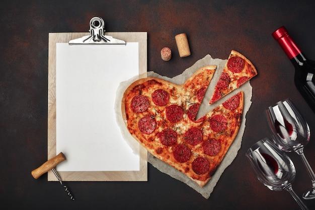 Pizza en forma de corazón con mozzarella, salchichas, botella de vino, dos copas de vino y tableta sobre fondo oxidado