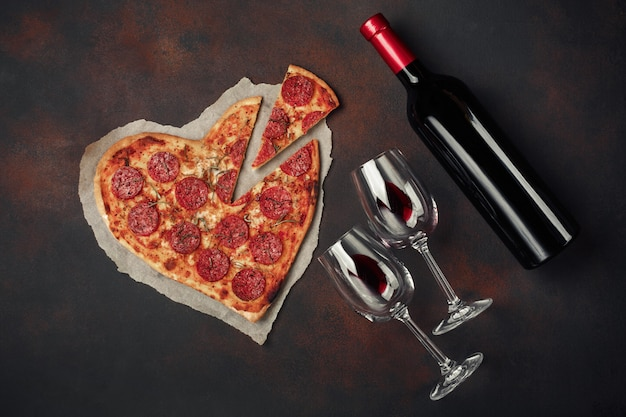 Pizza en forma de corazón con mozzarella, salchichas y botella de vino.