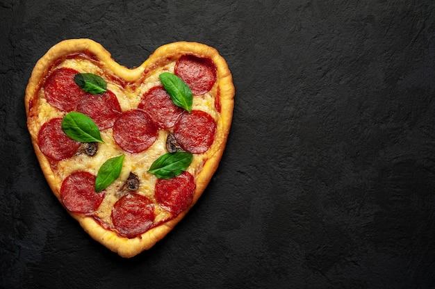Pizza en forma de corazón sobre una piedra negra. concepto de amor romántico de san valentín