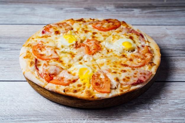 Pizza fresca en soporte de madera sobre la mesa.