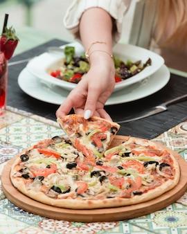 Pizza funghi con vegetales en la mesa