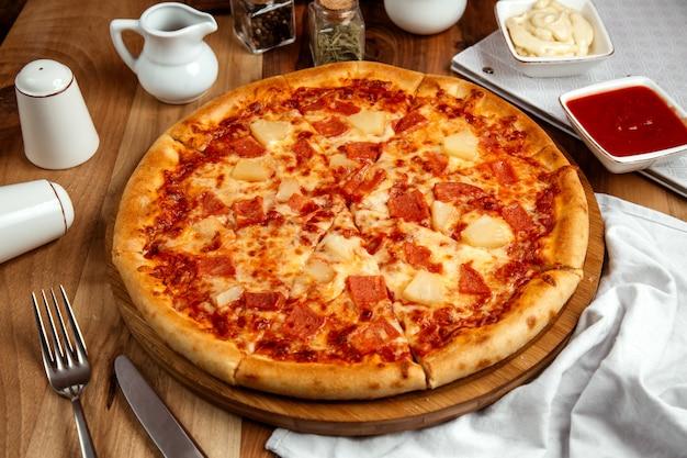 Pizza hawaiana con jamón cocido salsa de pizza queso y piña