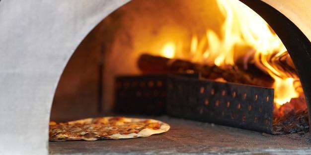 Pizza en horno de leña caliente para cocinar.