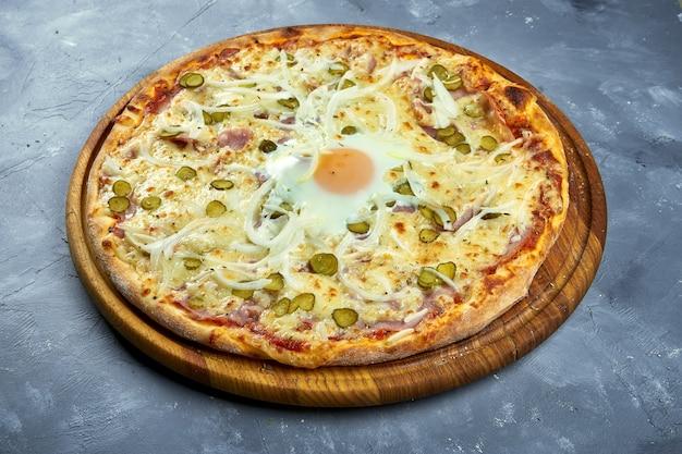 Pizza con huevo, queso, tocino y salsa cremosa sobre un fondo gris