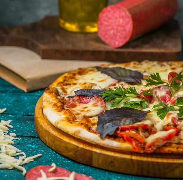 Pizza de ingredientes mixtos con hojas basílicas rojas y tomate.