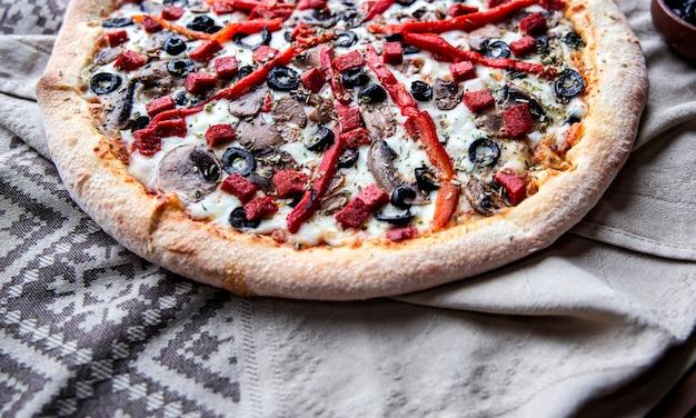 Pizza de ingredientes mixtos con pimiento rojo picado