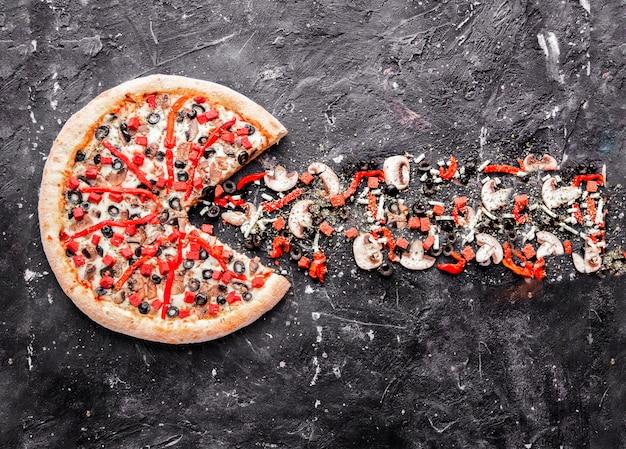 Una pizza de ingredientes mixtos con productos aislados en la piedra.