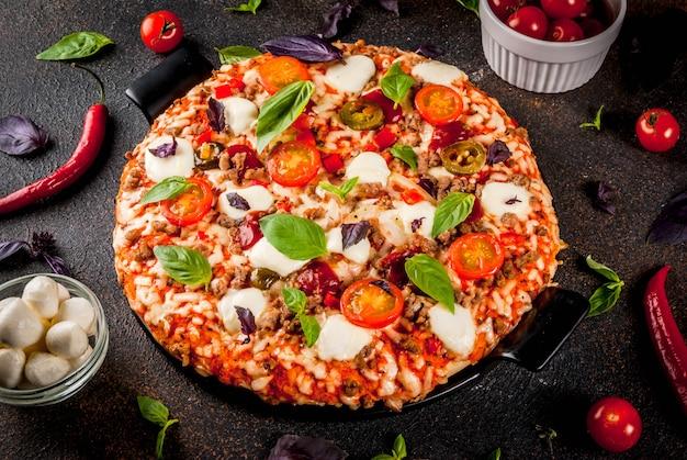 Pizza italiana a bordo de la parrilla con varios ingredientes sobre fondo oscuro