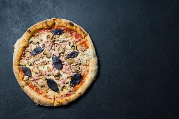 Pizza italiana con jamón, champiñones y albahaca.