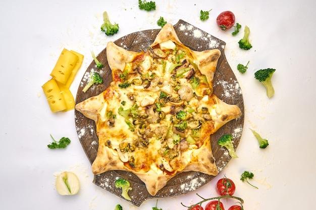 Pizza italiana de mariscos con mejillones, gambas, hierbas frescas, cebolla, queso mozzarella y champiñones en una tabla de madera