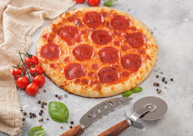 Pizza italiana de pepperoni al horno redonda fresca con cortador de rueda y cuchillo con tomates y albahaca sobre fondo de mesa de cocina ligera.