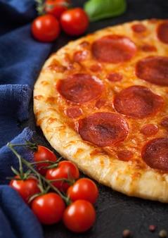 Pizza italiana de pepperoni al horno redonda fresca con tomates con albahaca sobre fondo negro de la mesa de la cocina.