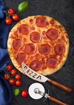 Pizza italiana de pepperoni horneada fresca redonda con cortador de rueda y cuchillo con tomate y albahaca sobre fondo negro de la mesa de la cocina.