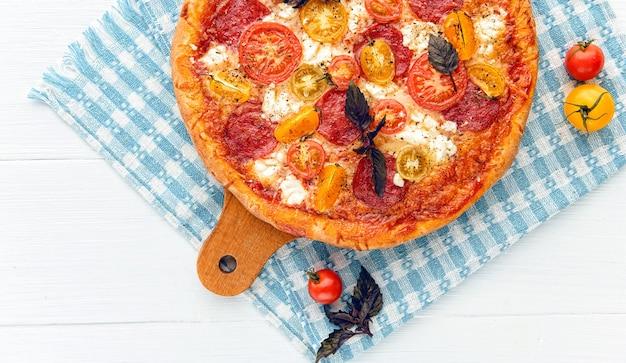 Pizza italiana de pepperoni con salami y queso sobre fondo blanco de madera rústica