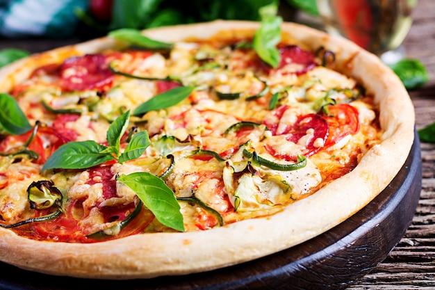 Pizza italiana con pollo, salami, calabacín, tomates y hierbas.