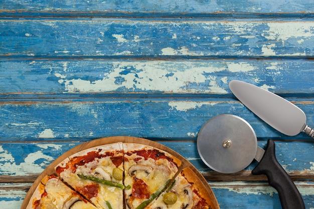 Pizza italiana servida en bandeja de pizza con cortador y cuchillo en tablón de madera