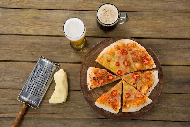 Pizza italiana servida en una bandeja de pizza con una jarra de cerveza y un vaso