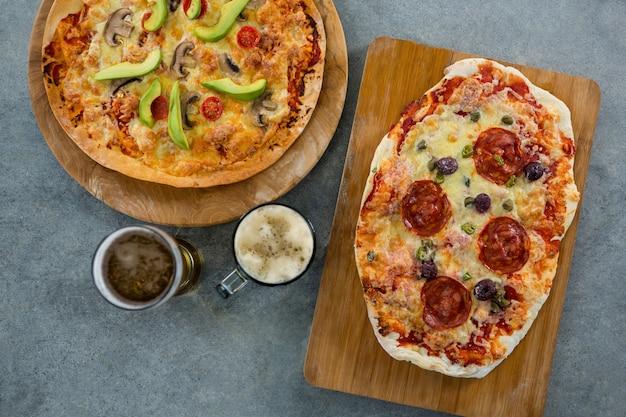 Pizza italiana servida en una tabla de cortar con una jarra de cerveza y un vaso