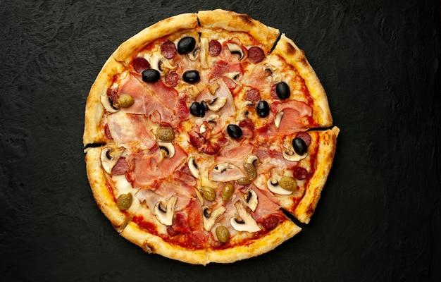 Pizza italiana con tocino, champiñones, aceitunas, tomates sobre un fondo de hormigón negro