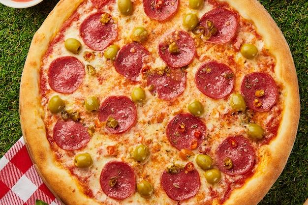 Pizza italiana tradicional pepperoni con salami, mozzarella, aceitunas y albahaca sobre fondo de hierba verde