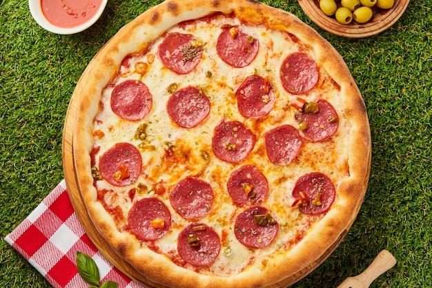 Pizza italiana tradicional pepperoni con salami, mozzarella y albahaca sobre hierba verde